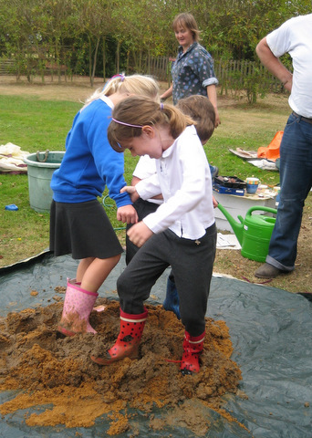 Children treading the mix for the Earth Oven