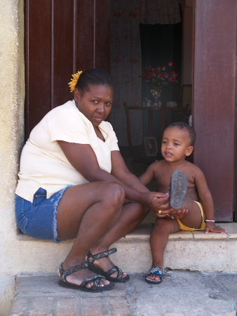 Mother fitting her child's sandals.
