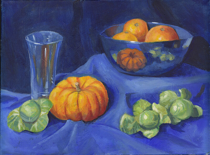 A still life featuring sprouts, a mini pumpkin and a tall glass on blue fabric. On a higher fabric-covered platform is a blue bowl with small oranges in it.