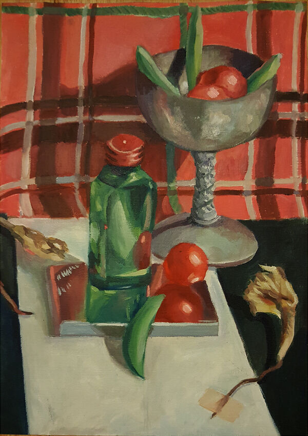 a small green bottle and silver goblet stand against a red tartan backdrop, surrounded by cherry tomatoes, mange tout and dying daffodils