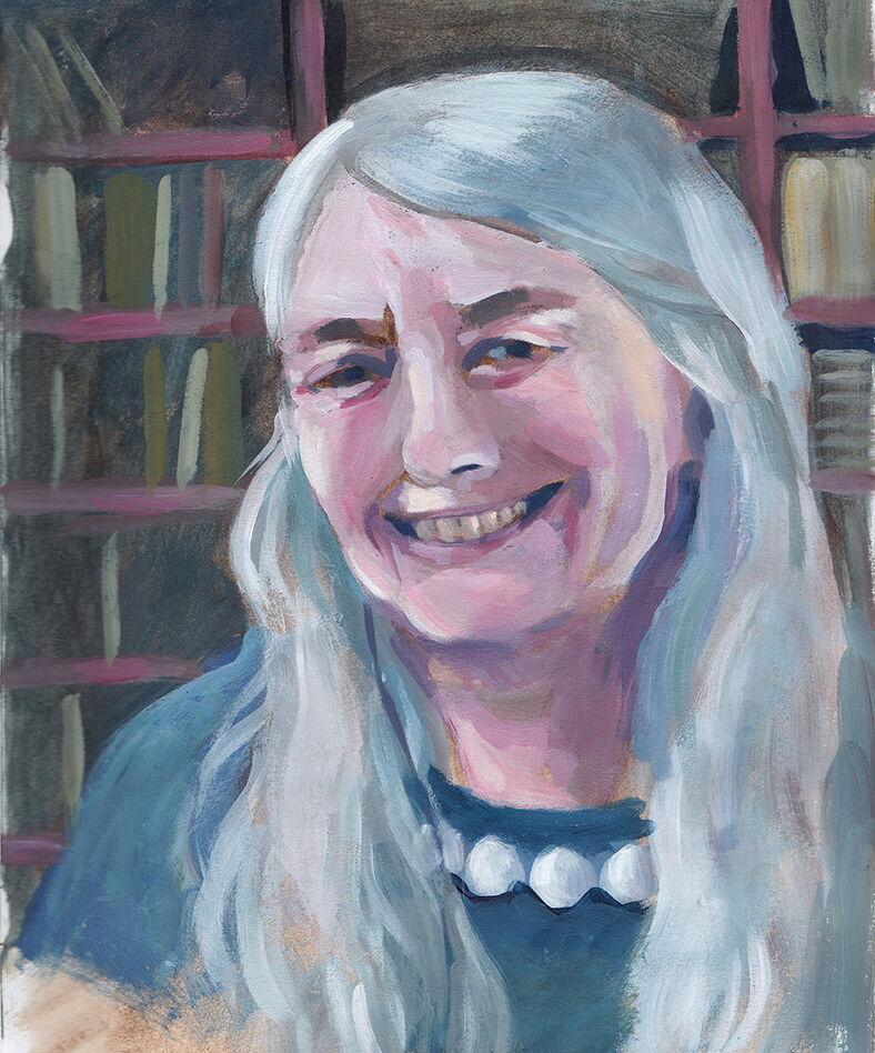 A portrait of historian Mary Beard, smiling, wearing a blue shirt. Behind her is a packed bookcase.
