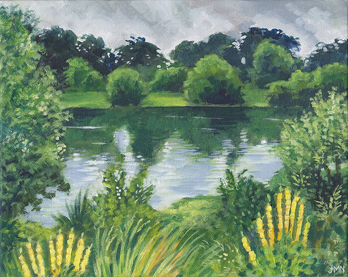 in the foreground, a vibrant green grassy bank with leafy plants and tall yellow flowers; beyond that, a calm lake, reflecting the green trees in the background, and the grey cloudy sky. just a few ripples break across the surface.