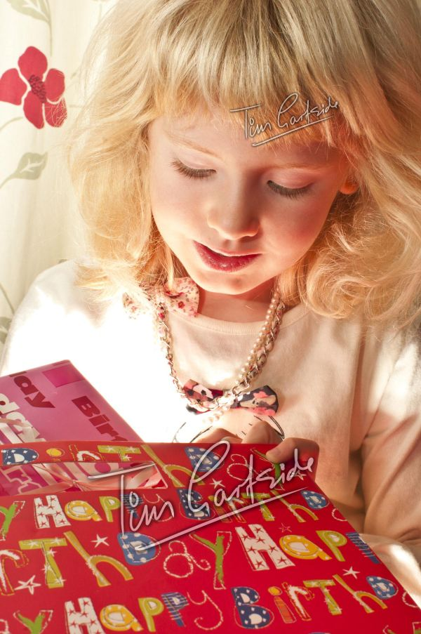 young girl opening present