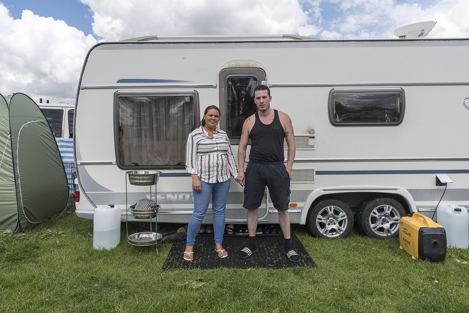 Couple in front of their caravan, Appleby Horse Fair, UK 2019
