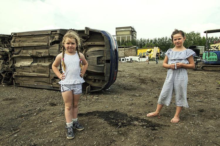 Girls in their father's scrapyard, roadside campsite, Limerick, Ireland 2018