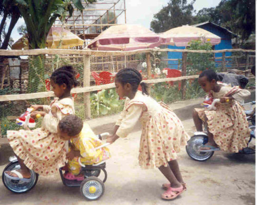 schoolgirls playing on the tricycles