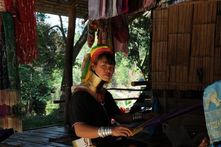 Young Padaung woman working at a loom