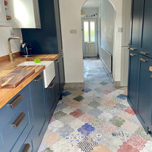 Spanish feel with mosaic floor tiles, arches and bright blue kitchen cabinets