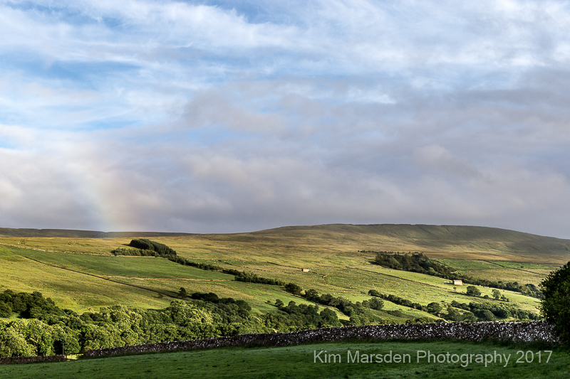 Coverdale in late evening light with the end of a rainbow