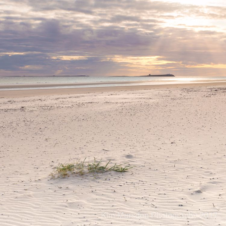 Early morning  sun breaking through over Farne Islands from Bamburgh beach