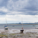 Lindisfarne harbour with Bamburgh Castle in the distance panorama