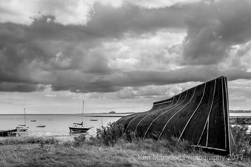 Lindisfarne boat with Bamburgh Castle in the distance - mono