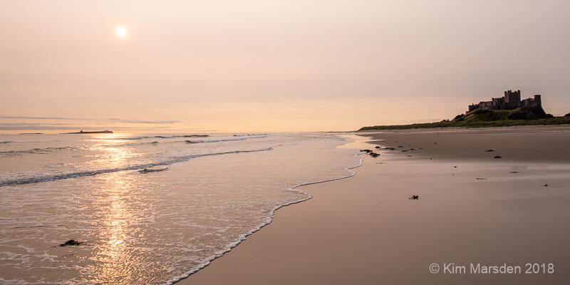 Morning light over Bamburgh beach