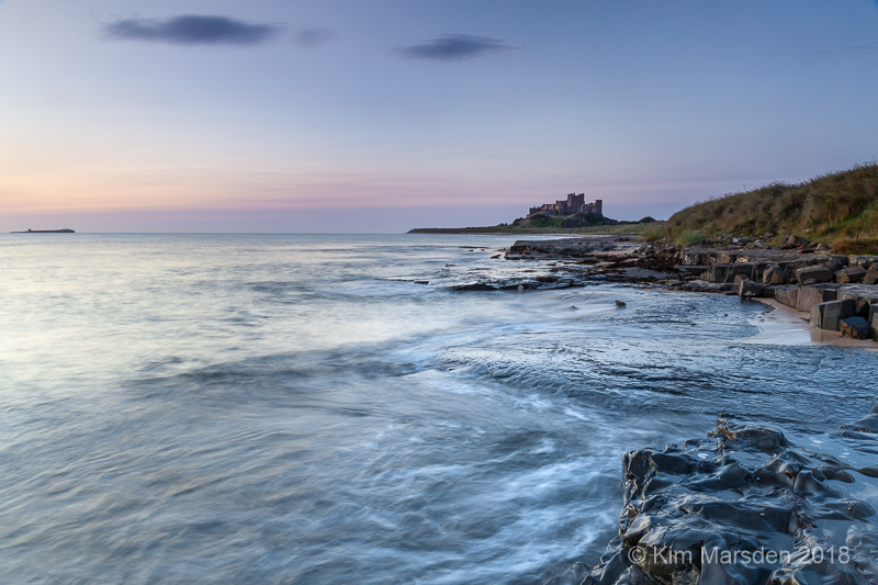 Bamburgh Castle lit by pre-dawn light