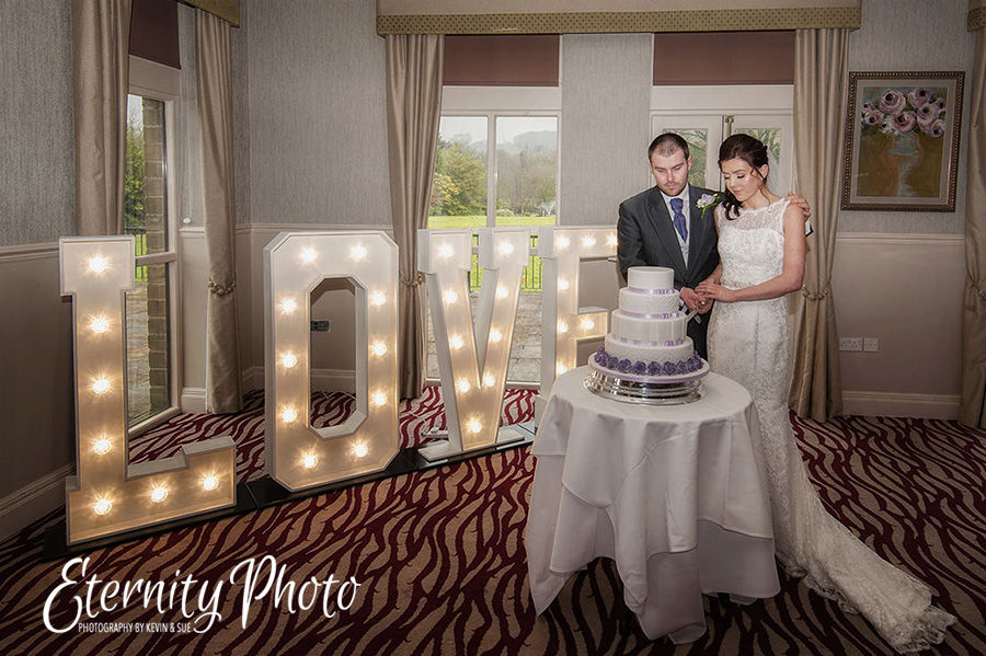 Bride and groom cutting the wedding cake by West Yorkshire wedding photographer