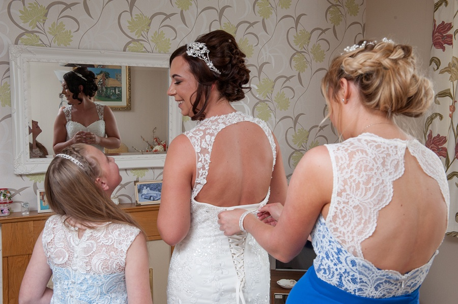 Wakefield wedding photography. The brides sister fastening the back of the bride's wedding dress during the bridal prep session.