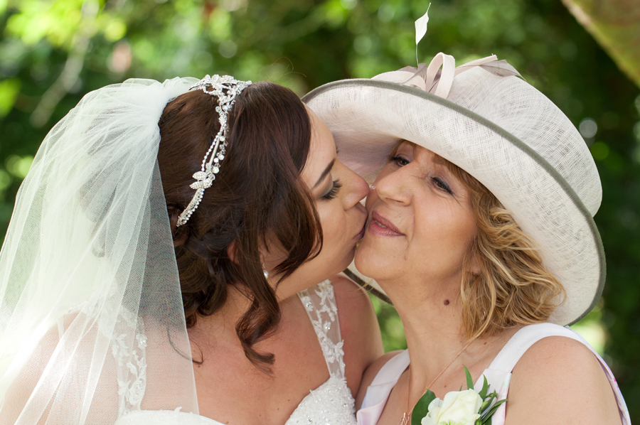 West Yorkshire wedding photographer.  The bride gives mother a kiss.
