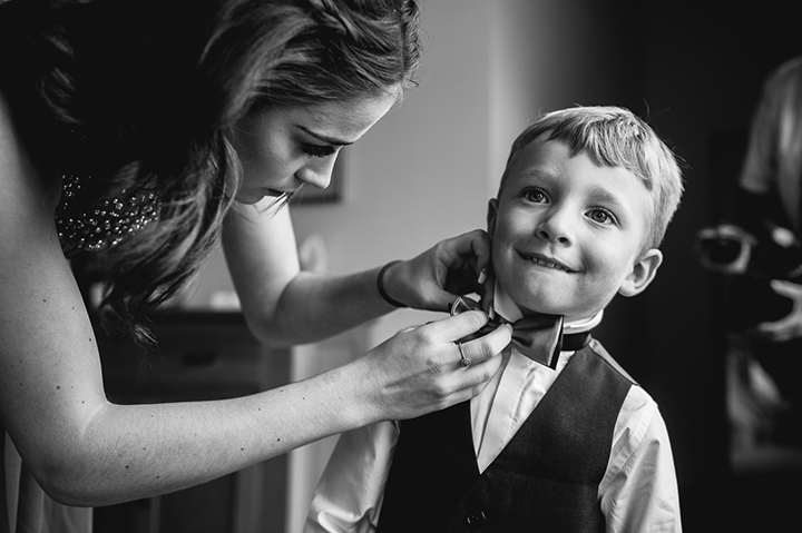 Worcestershire wedding photographer. A page boy has his bow tie done up by a bridesmaid before a Worcestershire wedding