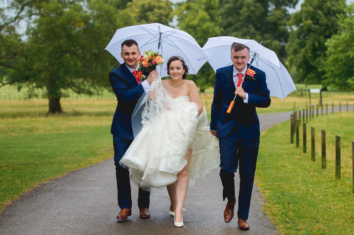 A bride and groom along with the best man walk down the main drive to Dumbleton Hall in the pouring rain after the wedding ceremony