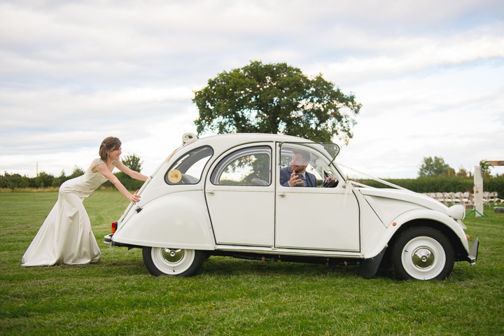 The groom steers as the bride lends a helping hand with a wedding car that won't start. The wedding car was a Citroen 2CV that was built from the ground up by the bride and groom.