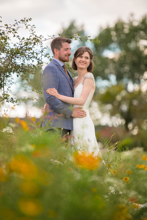 A bride and groom pose for photos in a wildflower meadow after their wedding at Rock Village hall near Kidderminster.