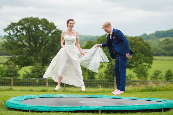 The bride and groom bounce on the trampoline at Bordesley Park in Worcestershire after their wedding