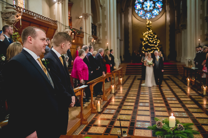 The bride makes her entrance into the great hall at Stanbrook Abbey. Her future husband can be seen waiting at the end of the isle.