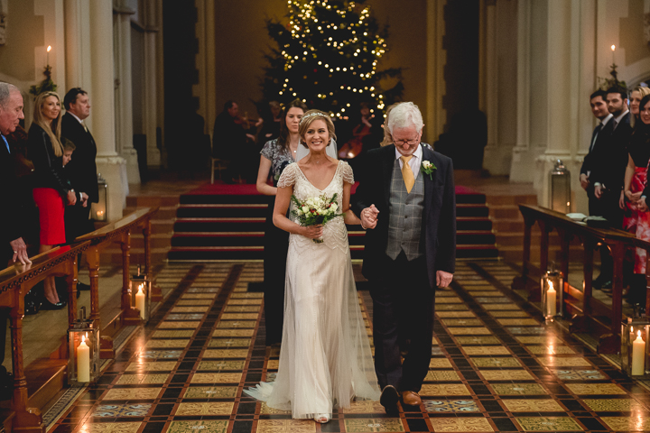 A bride walks down the aisle with her father at her side at Stanbrook Abbey in Worcestershire