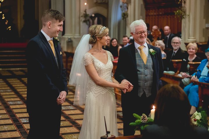A bride is given away by her father to her future husband during her wedding ceremony at Stanbrook Abbey in Worcestershire