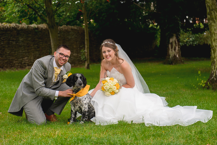 A bride and groom pose with their pet dog after their wedding ceremony at St Peters Church in Bromyard.