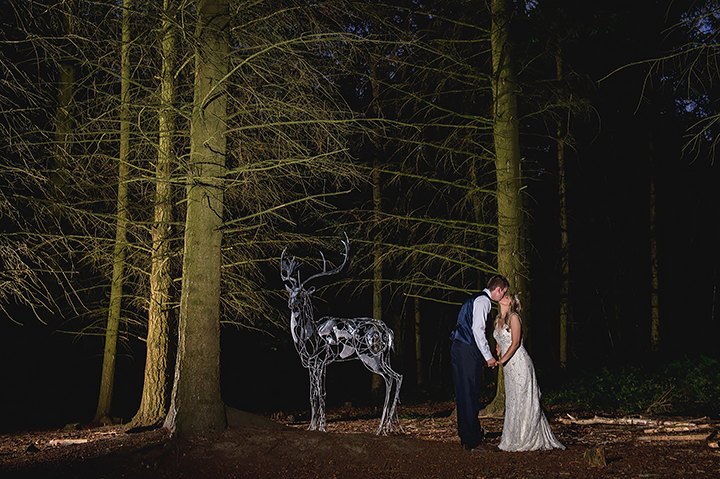 Wyre Forest wedding photography. A bride and groom kiss near a deer stag statue at Wyre Forest in Worcestershire