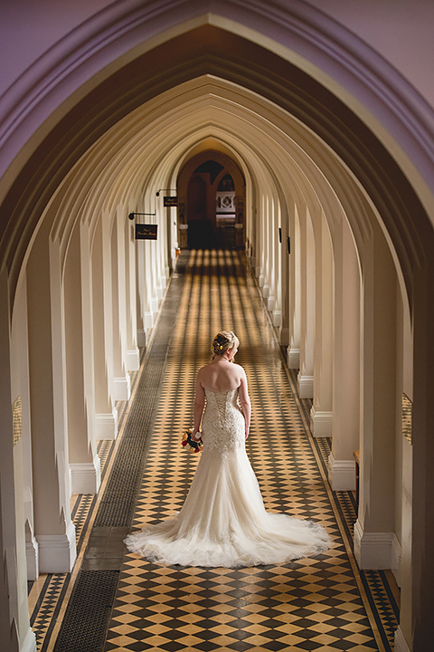 The bride stands in the cloisters of Stanbrook Abbey after her wedding.