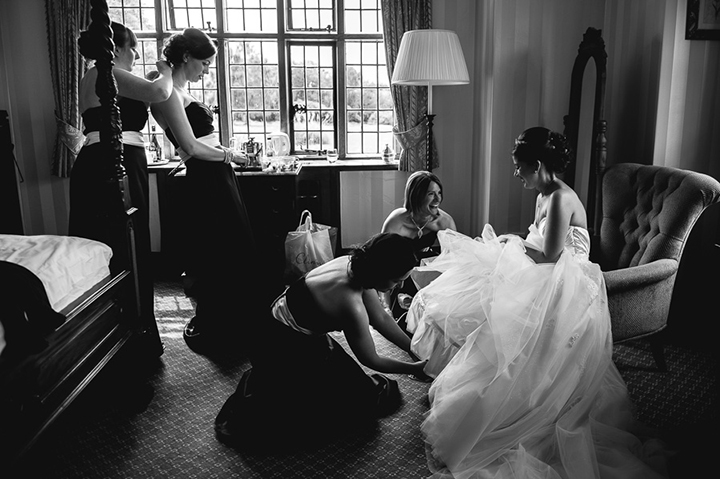 Stone Manor wedding photography. The bride has the final touches made to her wedding dress by her bridesmaids.