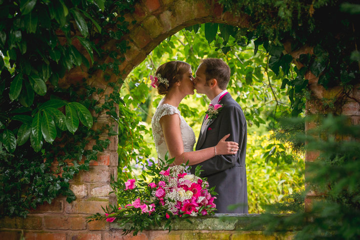Redhouse Barn wedding photography. The bride and groom kiss in the gardens of Red House Barn, Stoke Prior, Worcestershire.