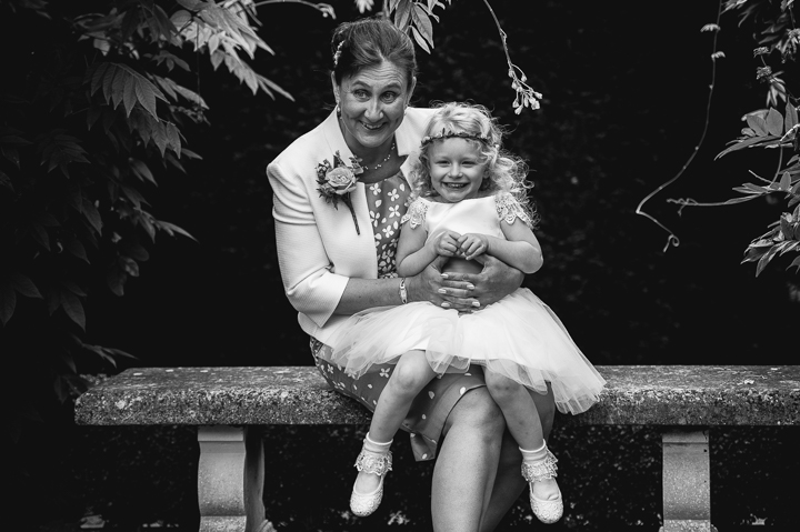 Birtsmorton Court wedding photography. A wedding guest holds a flowergirl on her lap during a wedding at Birtsmorton Court in Worcestershire