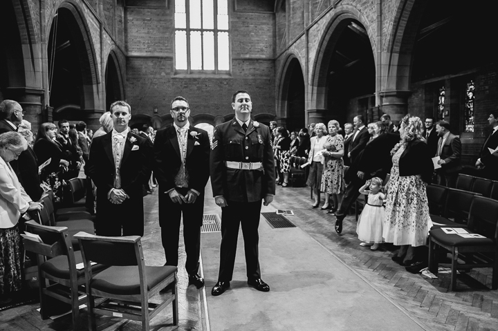 Worcestershire wedding photography. RAF Airman awaits the entrance of his bride before their wedding at St George's church in Worcester