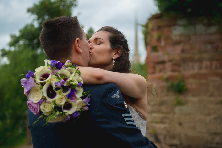 Worcester wedding photography. Wedding photo taken in the grounds of Worcester Cathedral near the River Severn. Worcester's St Andrews Needle can be seen in the background.