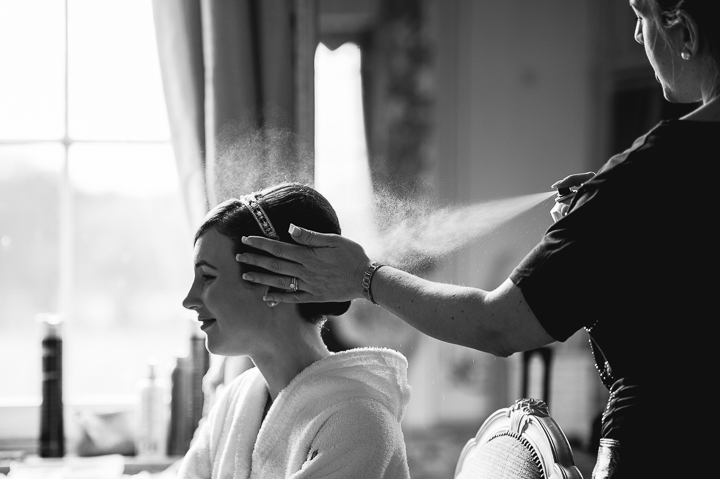 Gosfield Hall wedding photography. A bride has the final touches applied to her hair and tiara during her pre wedding preparations in the bridal suit of Gosfield Hall in Essex