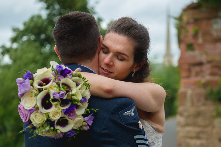Worcestershire wedding photography. The groom in RAF uniform embraces his new wife. Wedding photo taken in the grounds of Worcester Cathedral near the River Severn. Worcester's St Andrews Needle can be seen in the background.