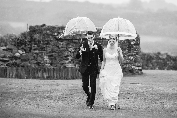 A bride and groom walk hand in hand in the rain at their Trevenna Wedding in Cornwall. Wedding Photography by Lee Webb