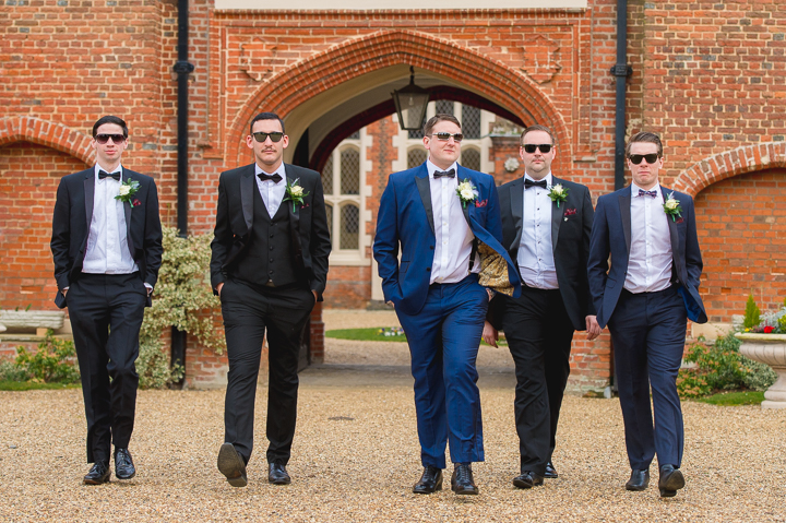 Gosfield Hall wedding photography. Often seen as a must have wedding photo, these groomsmen show their cool side whilst walking towards a wedding at Gosfield Hall in Essex.