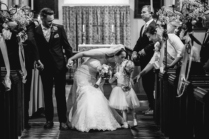 Birtsmorton Court wedding photography. A bride stops whilst walking down the aisle to kiss her flower girl at Birtsmorton Church in Worcestershire