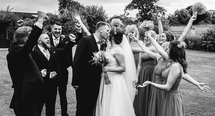 Worcestershire wedding photography. Groomsmen and bridesmaids celebrate as the bride and groom kiss after their wedding in Worcestershire