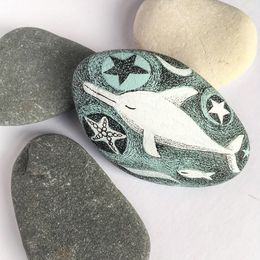 Dreamy Dolphin swimming while asleep. Handpainted Stone.