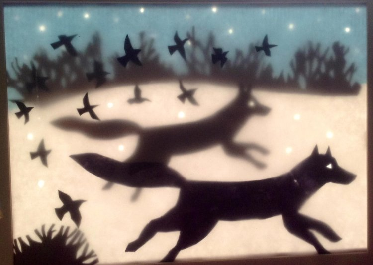 Running Wolves backlit in window.