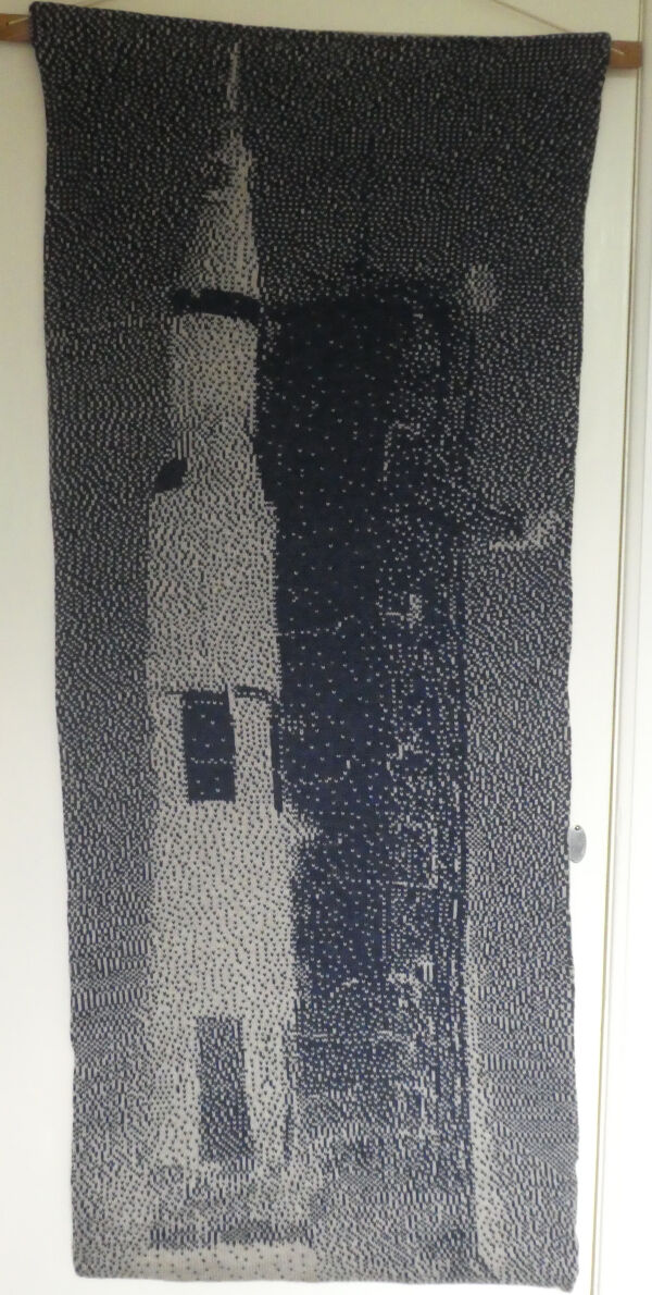 knitted image of Apollo 11's Saturn V lifting off. monchrome dark blue and grey
