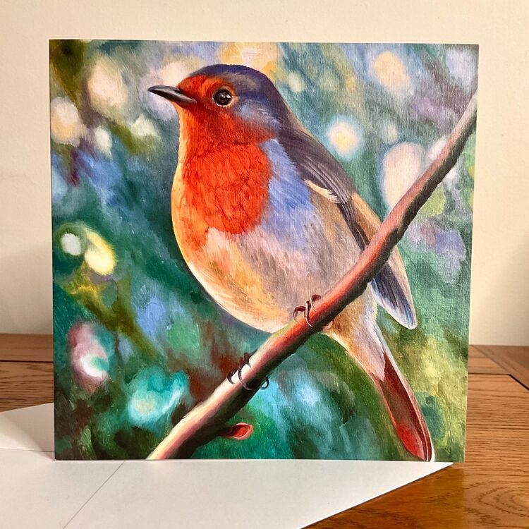 Greeting card with robin redbreast in the garden full of green and sunlight