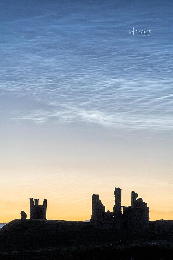 Noctilucent clouds over Dunstanburgh Castle, England