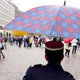Ticket Collector shelters under an umbrella, Berlin