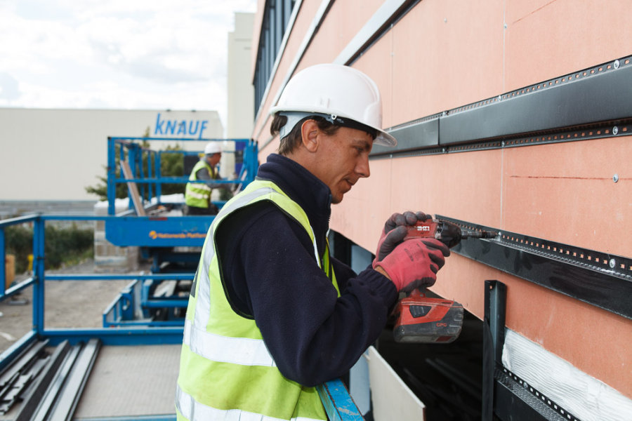 Worker Fixing ThermaFrame Wallboards<br>Knauf